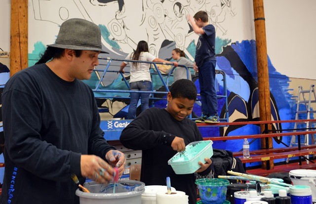 Mural artist Toma Villa, right, assisting students painting the new mural at Chief Kitsap Academy